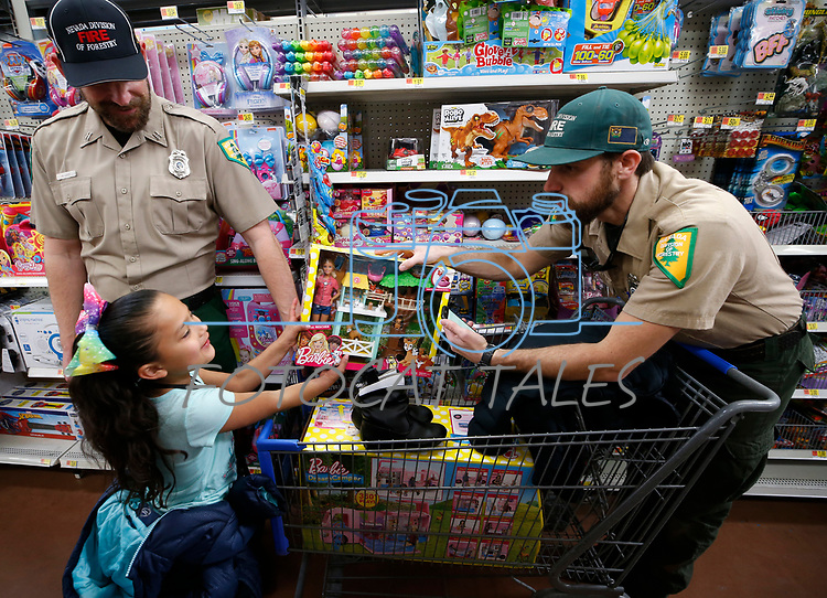 Michael Lucey, left, and Anthony Seghieri, with the Nevada Department of Forestry, help Brianna, 7, shop as part of the 15th annual Holiday with a Hero program at Walmart in Carson City, on Wednesday, Dec. 19, 2018. 240 K-8 students from the Carson City School District's McKinney-Vento program are paired with first responders for a $100 Christmas shopping spree. <br /> Photo by Cathleen Allison/Nevada Momentum