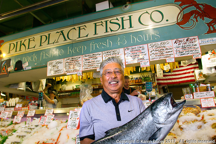 John Yokoyama, owner of Pike Place Fish Market holds a wild-caught King salmon from Alaska in Seattle, Wash., on July 1, 2013. Yokoyama has owned the market since 1965. (photo © karenducey.com)