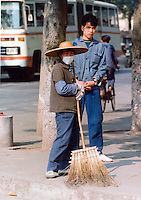 Street sweeper with onlooker  dressed in the typical blue overalls.Pictures taken in Canton China in 1977 at the time of the cultural revolution.