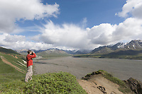 Hiker scans mountain horizon over the Thorofare river in Denali National Park, Alaska
