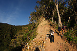 Trekking the steep climb to Wae Rebo village, serveral hours from road access.