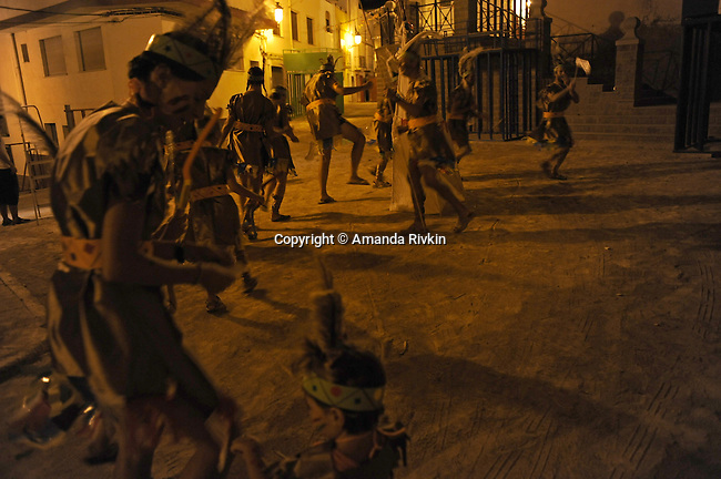 """Members of the """"penya,"""" or group of friends calling themselves """"Els Kutos,"""" or """"the pigs"""" in Catalan, step out in their Native American attire for Costume Night celebrations during the municipal fiestas in the town of Costur, Spain on August 17, 2009."""