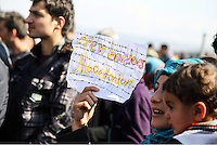 """Pictured: A migrant woman holding a piece of paper with a """"Open borders Macedonia""""  slogan Thursday 03 March 2016<br /> Re: Migrants have closed off the railway track at the Greek Fyro Macedonian border in Idomeni, Greece,"""