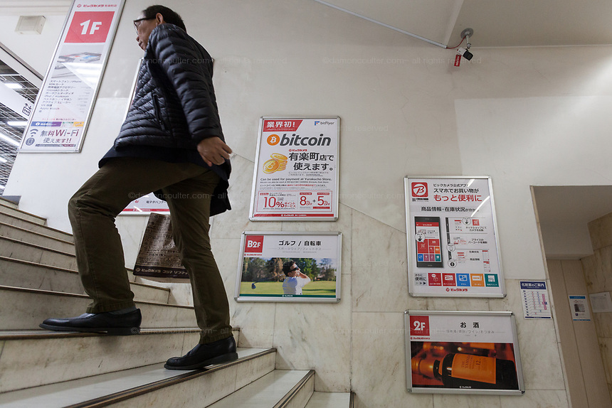 A Japanese salaryman climbs stairs next to a sign  advertising the ability to pay with bitcoins in Bic Camera, Yurakucho, Tokyo, Japan. Friday January 19th 2018. Japan elevated crypto-currencies  to the same status as other forms of money in March 2016 then in April 2017 allowed businesses to use Bitcoin as a legitimate form of payment. This led to large value hikes on this digital currency. Investing and using Bitcoins continues to gain popularity in Japan despite recent drops in their trading value..