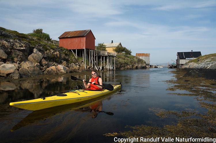 Dame padler kajakk ved det gamle fiskeværet på Villa i Flatanger ---- Girl kayaking on the Norwegian coast