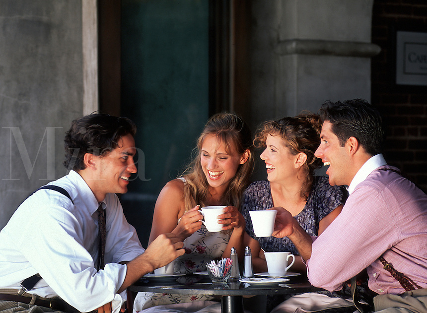 Two young couples laugh as they enjoy coffee in a cafe together.