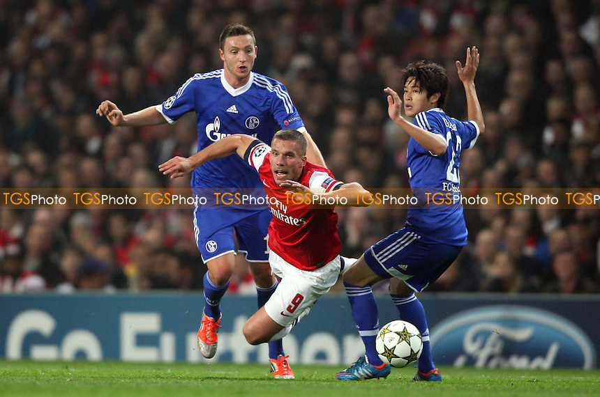 Luikas Podolski of Arsenal is fouled by Atsuto Uchida of Schalke  - Arsenal vs FC Schalke 04, Champions League Group B at The Emirates Stadium, Arsenal - 24/10/12 - MANDATORY CREDIT: Rob Newell/TGSPHOTO - Self billing applies where appropriate - 0845 094 6026 - contact@tgsphoto.co.uk - NO UNPAID USE.