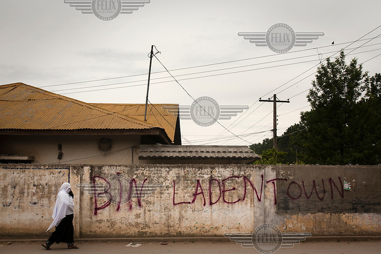 A woman walks past a spray-painted graffiti in Bilal Town, on the road leading to the compound where Osama Bin Laden was killed in an operation by US Navy Seals on 3 May 2011. Following the attack, code-named Operation Neptune Spear, American forces took bin Laden's body to Afghanistan for identification and then buried it in the Arabian Sea.