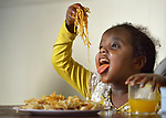 Five-year old Saliha Mussa, a recently arrived refugee from Eritrea, enjoys spaghetti for dinner in her family's apartment in Lancaster, Pennsylvania. The girl's family was resettled in the United States by Church World Service. <br /> <br /> Photo by Paul Jeffrey for Church World Service.