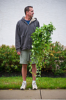 Gardener holding weeds pulled from the gardens lining a residential hotel poses for a photo as he nears completion of the garden cleaning.