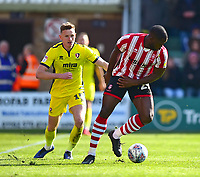 Lincoln City's John Akinde vies for possession with  Cheltenham Town's William Boyle<br /> <br /> Photographer Andrew Vaughan/CameraSport<br /> <br /> The EFL Sky Bet League Two - Lincoln City v Cheltenham Town - Saturday 13th April 2019 - Sincil Bank - Lincoln<br /> <br /> World Copyright © 2019 CameraSport. All rights reserved. 43 Linden Ave. Countesthorpe. Leicester. England. LE8 5PG - Tel: +44 (0) 116 277 4147 - admin@camerasport.com - www.camerasport.com