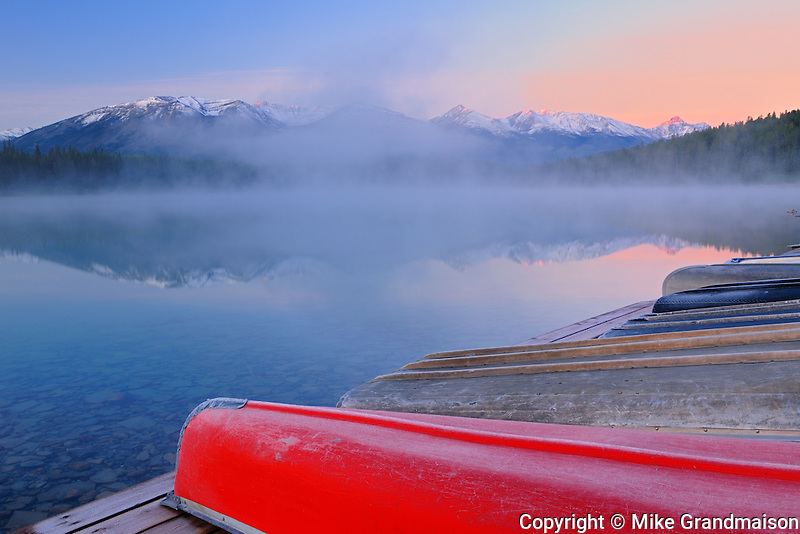 Canoes and Pyramid Lake in fog at dawn<br /> Jasper National Park<br /> Alberta<br /> Canada