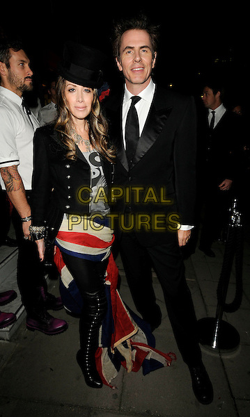 GUEST & ROGER TAYLOR .At the Juicy Couture flagship store launch party, Bruton Street, London, England, UK, 13th October 2009..full length black suit tie union jack skirt train tights boots studded over the knee clutch bag hat .CAP/CAN.©Can Nguyen/Capital Pictures.