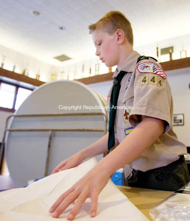 MIDDLEBURY CT. 03 May 2015-050315SV10-Ethan Harrington, 10, of Middlebury sets a table for the Boy Scout Troop 444 Pasta dinner at the firehouse in Middlebury. The fundraiser serves about 300 dinners and the proceeds pay for their camping trips and expenses through out the year. <br /> Steven Valenti Republican-American