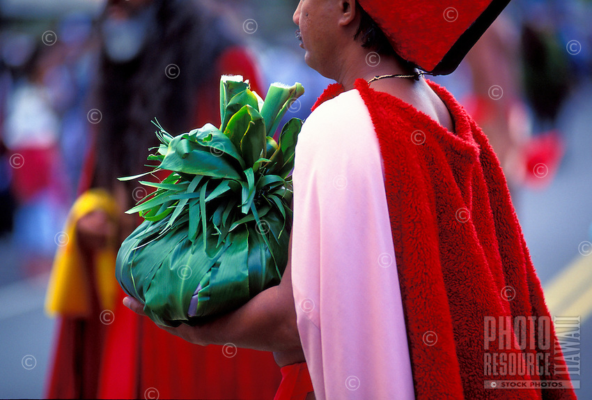 Man carries a hookupu ( ti leaf offering )  at an Aloha week festival ceremony