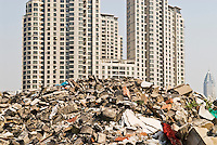 Rubble of demolished building with recently build apartment building in background, Shanghai, China