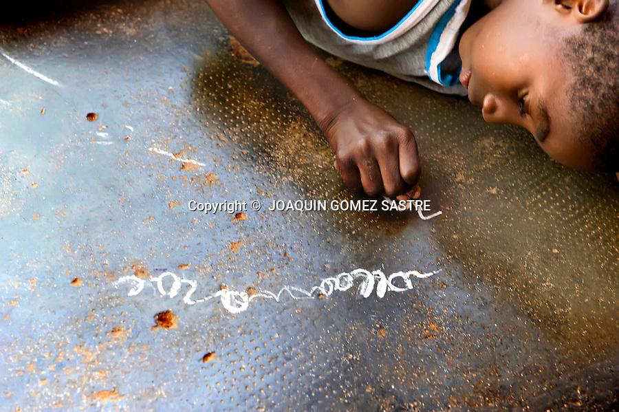 BOMBUAKA-TOGO-AFRICA 2010.Un niño escribe con una tiza en el suelo del centro Don Orione en Bombuaka (TOGO).foto © JOAQUIN GOMEZ SASTRE