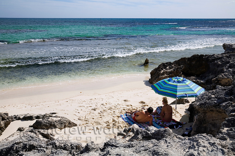 A couple relax under a beach umbrella at The Basin - a popular swimming beach on Rottnest Island, Western Australia, AUSTRALIA.