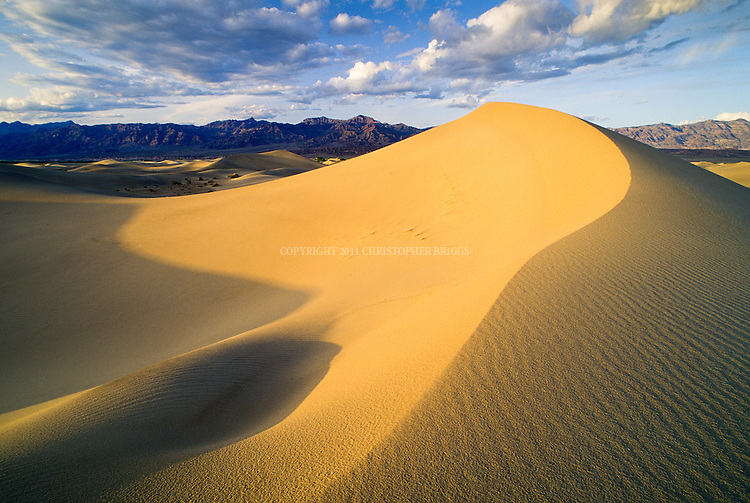Primary source of the sand is Cottonwood Mountains to the north and northwest, providing tiny grains of quartz, feldspar and magnetite that form the sand. Roughly fifteen-square-miles of dunes includes three types of sub-barchan (modified crescent) dunes: crescent, linear, and star shaped. Highest dunes 130–140 ft (40–43m). Grapevine Mountains in background. Death Valley National Monument Est. February 11, 1933. Est. as Death Valley National Park in 1994; 5,270 square miles (13,649 km2). Inyo County, CA.