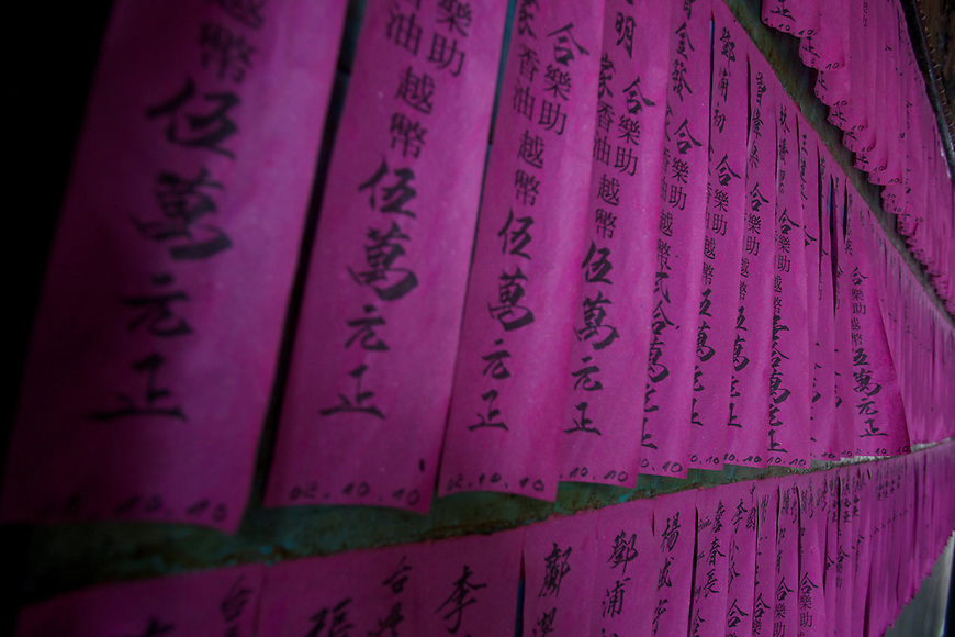 The pink tissue paper prayer flags, contain the names of people who have made donations for the upkeep of the temple, at Chùa Bà Thiên H?u (The Pagoda of the Lady Thien Hau), Ho Chi Minh City, Saigon, Vietnam