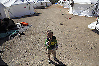 Pictured: A young boy stands by a row of tents Friday 26 February 2016<br />