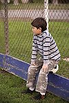 Young boy with soccer ball leaning on fence