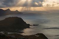 Light rays shine through clouds over coastal mountains, Vestvågøy, Lofoten Islands, Norway