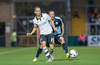 Kay Voser of Fulham passes the ball back under pressure from Michael Harriman of Wycombe Wanderers during the Capital One Cup match between Wycombe Wanderers and Fulham at Adams Park, High Wycombe, England on 11 August 2015. Photo by Andy Rowland.