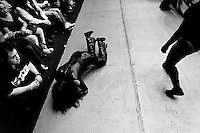 "A female Lucha libre wrestler lies on the floor outside the ring after being knocked down during a fight at Arena Mexico in Mexico City, Mexico, 26 April 2011. Lucha libre, literally ""free fight"" in Spanish, is a unique Mexican sporting event and cultural phenomenon. Based on aerial acrobatics, rapid holds and the use of mysterious masks, Lucha libre features the wrestlers as fictional characters (Good vs. Evil). Women wrestlers, known as luchadoras, often wear bright shiny leotards, black pantyhose or other provocative costumes. Given the popularity of Lucha libre in Mexico, many wrestlers have reached the cult status, showing up in movies or TV shows. However, almost all female fighters are amateur part-time wrestlers or housewives. Passing through the dirty remote areas in the peripheries, listening to the obscene screams from the mainly male audience, these no-name luchadoras fight straight on the street and charge about 10 US dollars for a show. Still, most of the young luchadoras train hard and wrestle virtually anywhere dreaming to escape from the poverty and to become a star worshipped by the modern Mexican society."