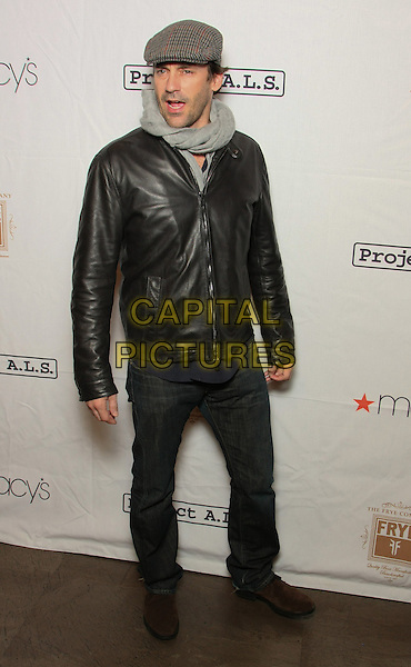 """JON HAMM.The 13th Annual Project A.L.S. """"Tomorrow Is Tonight"""" Benefit at Lucky Strike Lanes & Lounge, New York, NY, USA..October 21st, 2010.full length black leather jacket grey gray scarf flat cap hat jeans denim mouth open.CAP/LNC/TOM.©LNC/Capital Pictures."""
