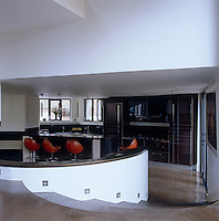 Polished curved concrete steps snake around the sunken den and lead from the dining area to the ebony kitchen