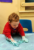 MR / Schenectady, New York. Schenectady Day Nursery (private nonprofit daycare). Toddler class. Girl (Age 2) cleans table after art project using shaving cream and food coloring. MR: Rob5. © Ellen B. Senisi