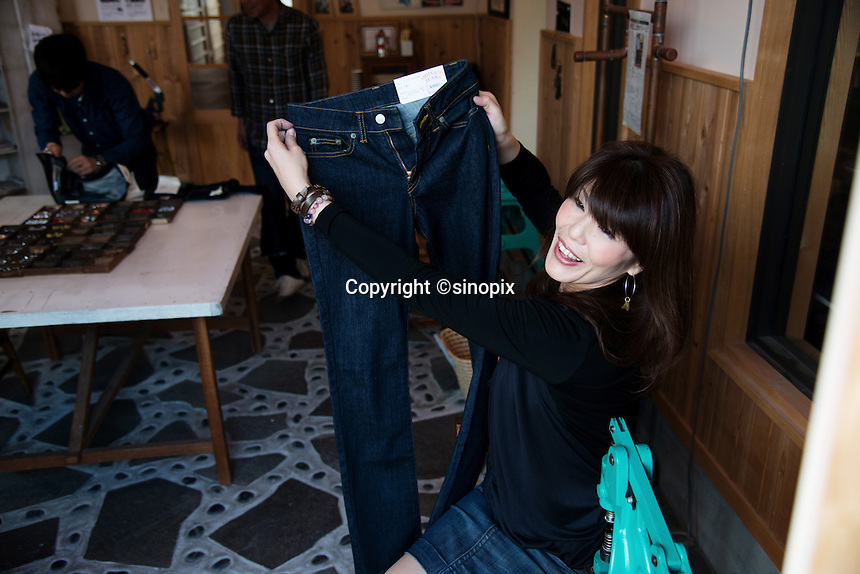 MAY 15, 2014 - KOJIMA, KURASHIKI, JAPAN: Visitors experience customizing jeans they purchased at Betty Smith CO.(Photograph / Ko Sasaki)