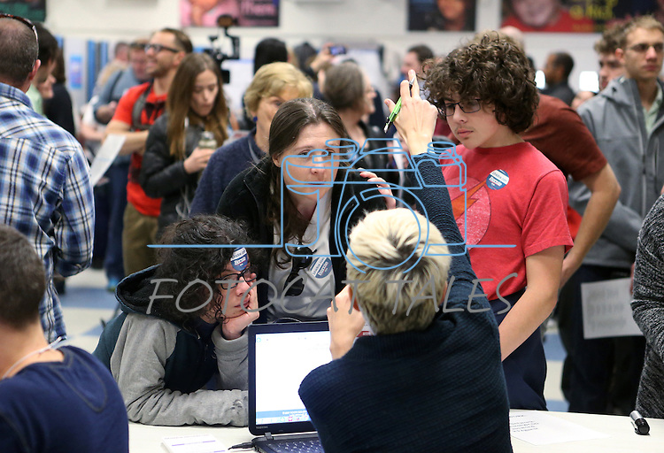 Jenny McKay and her sons Marco, left, and Hernan Perez, listen to check-in instructions at the Democratic Caucus at Libby Booth Elementary School, in Reno, Nev. on Saturday, Feb. 20, 2016. Cathleen Allison/Las Vegas Review-Journal