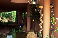 Two african tribal snake sculptures stand at the edge of a pool which twists and turns underneath the house into the main garden