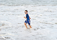Boy playing in the ocean surf.