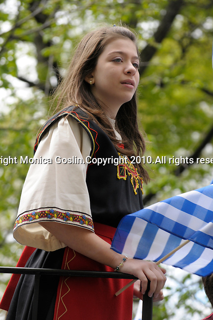 Greek Parade in New York City. A girl in traditional clothes and holding a Greek flag, rides a float in the Greek Parade in New York City.