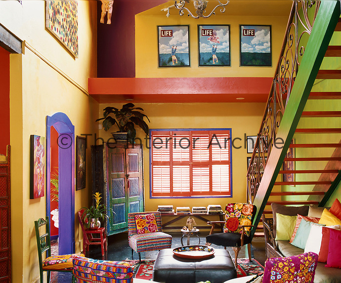 The vibrant living room is reached via a wrought-iron staircase and is filled with a collection of vivid textiles, upholstered furniture and artworks