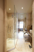Polished sandstone covers the floors and walls of this elegant shower room