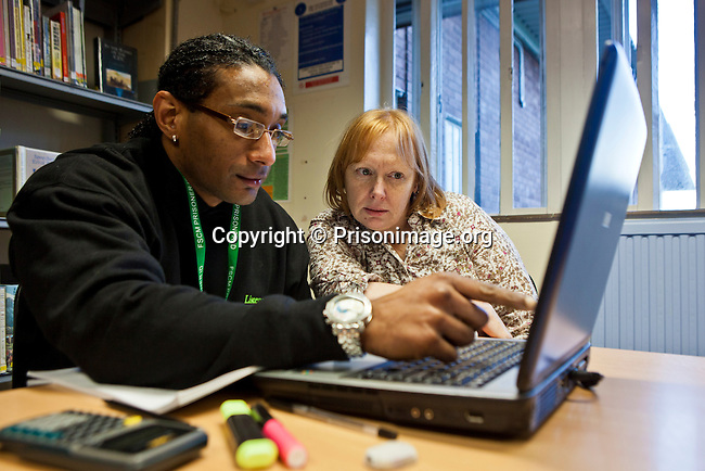 Assisted by a tutor a student sits working on a laptop in the prison library. Open University are working with prisoners in the education department at HMP Featherstone.
