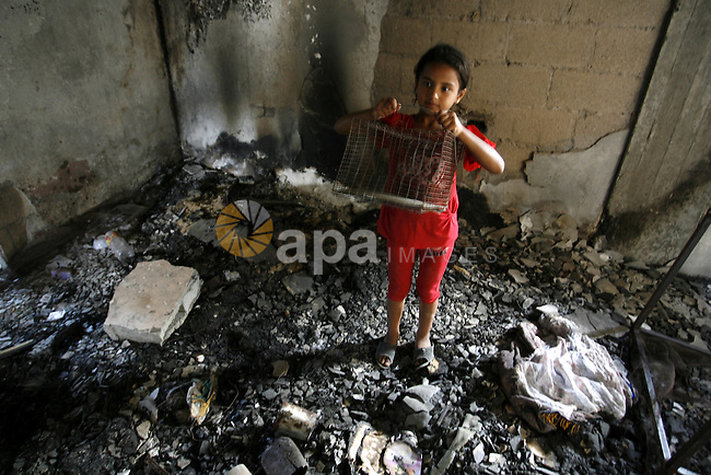 "A Palestinian girl searches in a destroyed house in Khan Yunis in the southern Gaza Strip on September 11, 2014. Israel's deputy foreign minister,Tzahi Hanegbi , warned that Hamas was likely to resume ""violence"" if it feels it has made no political gains from upcoming talks in Cairo. Photo by Abed Rahim Khatib"