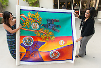 From left, Jacqueline Ayala '14 and Bianca Fonseca Cervantes '14 unroll the finished Educational Empowerment Mural before installation in the Academic Commons on May 6, 2014. Highland Park artist Pola Lopez, the two students and other volunteers helped create the mural. (Photo by Marc Campos, Occidental College Photographer)