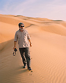 OMAN, Middle East,  Muscat, mature man walking in Wahiba Sands, holding camera