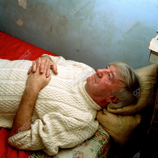 Charlie lies down in his bed in the room that he rents from Paddy, 2003