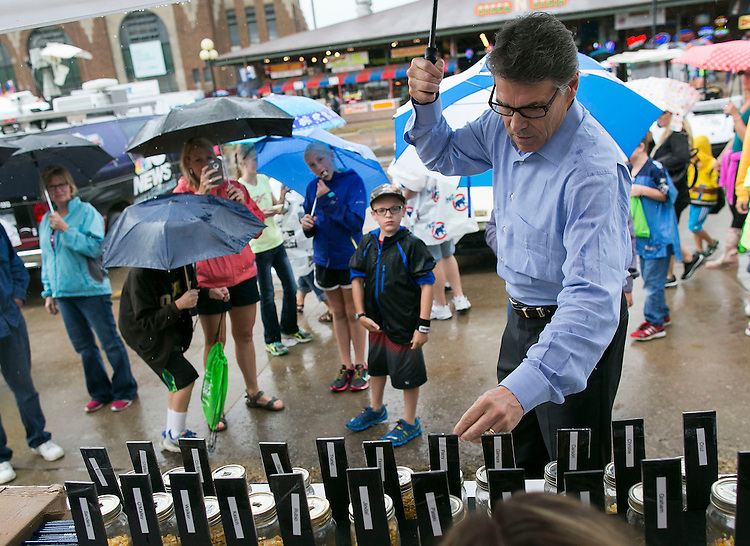 UNITED STATES - August 17: Republican presidential candidate Rick Perry casts his kernel of corn at the  &quot;Cast Your Kernel&quot; poll at the Iowa State Fair on Tuesday, August 18, 2015 in Des Moines, Iowa. Each fairgoer is given one kernel to vote for their presidential choice. As of Tuesday, GOP hopeful Donald Trump leads the overall poll with 7,003, or 23% of the votes ahead of Democratic hopeful Hillary Clinton, with 5,419, or 18% of the 30,495 votes cast.<br /> <br /> <br />  (Photo By Al Drago/CQ Roll Call)