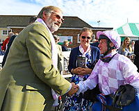 Jockey John Egan shakes hands with connections of Dark Optimist in the Winners enclosure  after winning The George Smith Horseboxes British EBF Maiden Stakes  during Evening Racing at Salisbury Racecourse on 25th May 2019