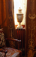 The fabric used on the armchair and curtains echoes the design featured on the urn balanced on a radiator in the window
