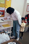 Palo Alto CA, Shy, three-year-old looking over preschool while mom signs her in  MR