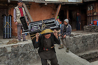 A porteur carries a stove to a remote village. Thulo Bharkhu, Nepal. 09 May 2013
