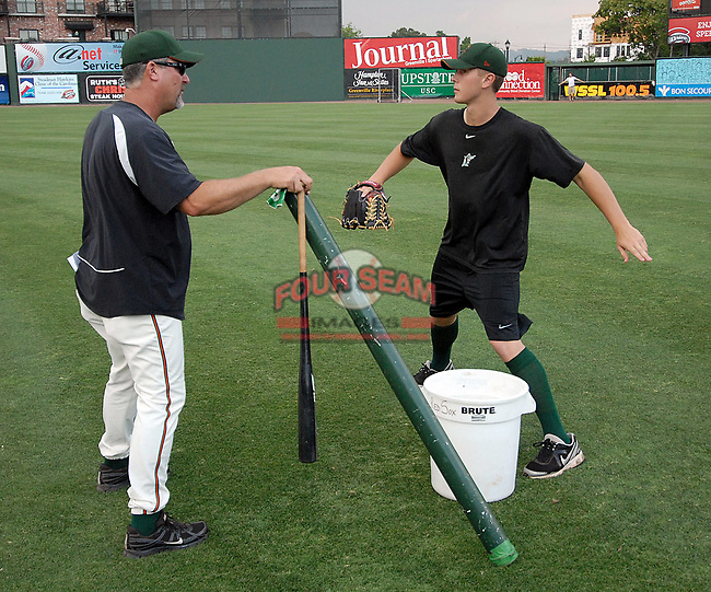 Pitching coach Charlie Corbell (25), left,  of the Greensboro Grasshoppers uses a bucket to show LHP Chad James (33) how high he wants him to pick up his legs on his follow through in a session prior to a game against the Greenville Drive on June 14, 2010, at Fluor Field at the West End in Greenville, S.C. Photo by: Tom Priddy/Four Seam Images